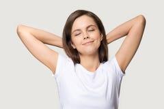 Vreedzame vrouw die handen zetten die achter hoofd op grijze achtergrond wordt geïsoleerd royalty-vrije stock afbeeldingen