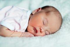 Vreedzame zoete pasgeboren zuigelingsbaby die op bed liggen terwijl het slapen in een heldere ruimte royalty-vrije stock afbeeldingen