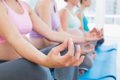 Vreedzame zwangere vrouwen die in yogaklasse mediteren stock afbeeldingen