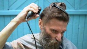 Vreemde hipstermens die met grote grijs-haired baard en belachelijk grimas eigen haar met scheerapparaatclipper proberen te snijd stock video