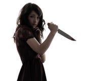 Vreemde jonge vrouwenmoordenaar die bloedig messensilhouet houden stock foto's