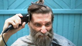 Vreemde mens met baard die eigen haar met clipper proberen te snijden stock videobeelden