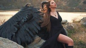 Vreselijk duivels boodschappersvoer op energie van zon, meisje van Satan met grote zwarte sterke vleugels en scherpe hoornen op h stock video