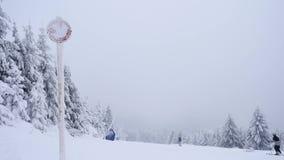 Vreselijk nevelig weer op helling in de winterbergen Weinig skiërs onderaan heuvel het ski?en De skitoevlucht van de de winterber stock video