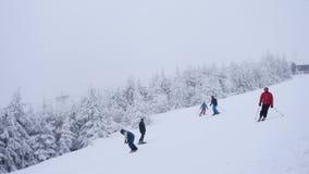 Vreselijk nevelig weer op helling in de winterbergen Weinig skiërs onderaan heuvel het ski?en De skitoevlucht van de de winterber stock videobeelden