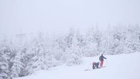 Vreselijk nevelig weer op helling in de winterbergen Weinig skiërs onderaan heuvel het ski?en De skitoevlucht van de de winterber stock footage