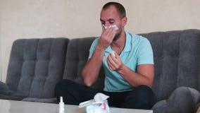 Vreselijke allergie Gefrustreerde knappe jonge mens die en weefsel gebruiken terwijl thuis het zitten op de laag niezen stock footage