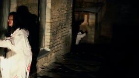 Vreselijke zombieën die langzaam in donkere backstreet lopen, die slachtoffers zoeken bij nacht stock video