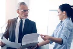 Vresig chef och hans kvinnlig kontorsarbetare som argumenterar över dokument Arkivbilder