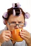 Vresig kvinna i hårrullar som dricker kaffe i morgonen Royaltyfria Bilder