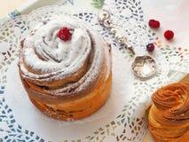 Vresig muffin med tappningskeden och röda bär på den vita doilyen arkivbild