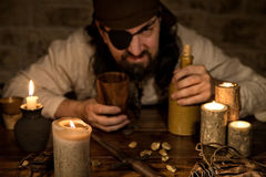 Vresigt piratkopiera med en flaska av romsammanträde på en medeltida tabell Royaltyfri Bild