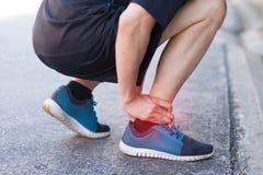 Vriden för löpare rörande smärtsam eller bruten ankel Olycka för idrottsman nenlöpareutbildning Stukar den rinnande ankeln för sp royaltyfria foton