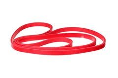 Vriden röd rubber handledmusikband som isoleras på vit Royaltyfri Foto
