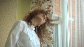 Vrider lockigt hår för flickan, aktivt hennes huvud som är skämtsamt, lyssnar till musik i hörlurar vid fönstret, telefonen i hen lager videofilmer