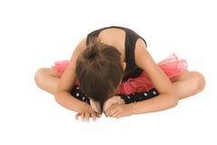 Vridet över huvudet för ung ballerinaflicka trycka på hennes fot Royaltyfria Bilder