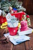 Vridna räkningar av dollar och euro i röd jul ösregnar, euro- och rosa färgmakron Gåvor för ` s för nytt år Arkivbilder