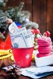 Vridna räkningar av dollar och euro i röd jul ösregnar, euro- och rosa färgmakron Gåvor för ` s för nytt år Fotografering för Bildbyråer