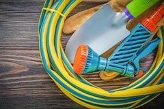 Vridna trädgårds- rubber slangsäkerhetshandskar räcker spaden på den wood galten Royaltyfri Fotografi