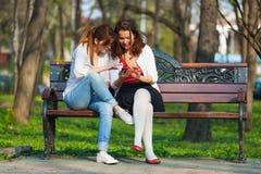 Vriend die pret hebben die een mobiele telefoon met behulp van Stock Foto