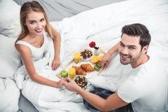 Vriend en meisje die ontbijt in het bed hebben royalty-vrije stock foto's