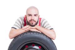 Vriendelijke en vriendschappelijke jonge werktuigkundige die op de band van het autowiel rusten Royalty-vrije Stock Afbeelding
