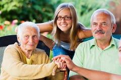 Vriendelijke Familie die Bejaarde Dame bezoeken Stock Foto