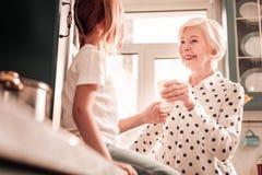 Vriendelijke oma die haar kleindochter met liefde bekijkt stock afbeelding