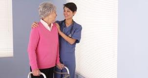 Vriendelijke verpleegster en bejaarde patiënt die zich door venster te spreken bevinden Royalty-vrije Stock Foto's
