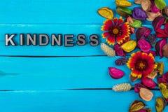 Vriendelijkheidswoord op blauw hout met bloem stock afbeelding