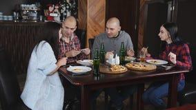 Vrienden bij de lijst in de pizzeria die op foto's bij smartphone en het glimlachen letten stock footage