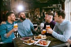 Vrienden bij Diner het Drinken Bier en het Eten van Voedsel bij Restaurant stock fotografie