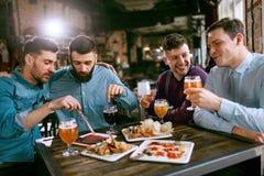 Vrienden bij Diner het Drinken Bier en het Eten van Voedsel bij Restaurant royalty-vrije stock afbeelding