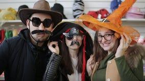 Vrienden dansen die de camera in een Carnaval-supermarkt van hoedenkerstmis bekijken stock video