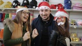 Vrienden dansen die de camera in een Carnaval-supermarkt van hoedenkerstmis bekijken stock footage