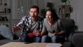 Vrienden die aan een elektriciteitspanne lijden tijdens TV-sportengelijke stock videobeelden