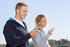 Vrienden die aan muziek op hun hoofdtelefoons luisteren stock foto