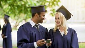 Vrienden die in academische regalia de zomerbaan zoeken bij cellphone, die post controleren royalty-vrije stock foto's
