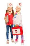 Vrienden die artsen met stuk speelgoed eerste hulpuitrusting spelen Stock Afbeelding