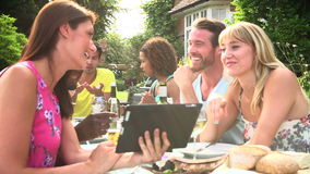 Vrienden die Barbecue hebben die thuis Digitale Tablet bekijken stock footage