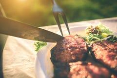 Vrienden die barbecue maken en lunch in de aard hebben Paar die pret hebben terwijl het eten en het drinken bij een Gelukkige pic royalty-vrije stock fotografie