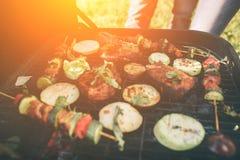 Vrienden die barbecue maken en lunch in de aard hebben Paar die pret hebben terwijl het eten en het drinken bij een Gelukkige pic royalty-vrije stock foto's