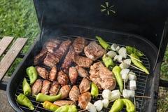 Vrienden die barbecue maken en lunch hebben Royalty-vrije Stock Afbeeldingen