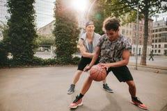 Vrienden die basketbal op hof spelen en pret hebben Royalty-vrije Stock Foto