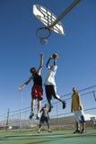 Vrienden die Basketbal spelen tegen Blauwe Hemel Royalty-vrije Stock Foto's