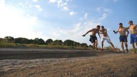Vrienden die bij de landweg lopen en pret hebben Groep gelukkige jongensdwaas rond in openlucht Front View stock video