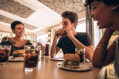 Vrienden die bij een snel voedselrestaurant samenkomen royalty-vrije stock fotografie