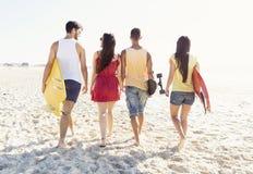 Vrienden die bij het strand lopen Stock Foto's