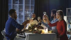 Vrienden die bij lijst aangaande Thanksgiving day roosteren stock foto