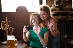 Vrienden die bij smartphone golven stock foto